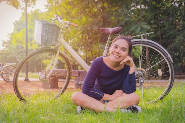 Szczęśliwy młody azjatykci kobiety obsiadanie z starym białym bicyklem. w parku.