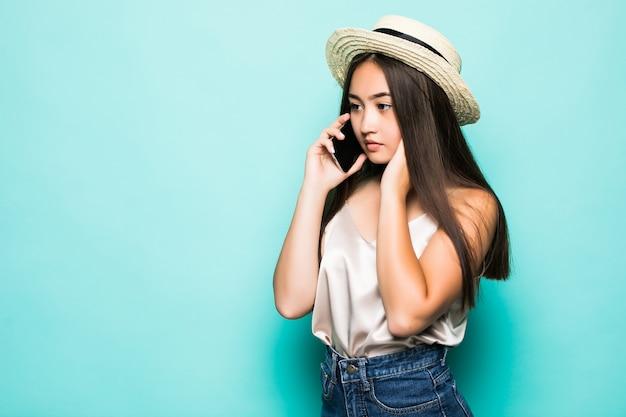 Szczęśliwy młody azjatykci kobiety pozować odizolowywam nad turkusowym tłem opowiada telefonem komórkowym.