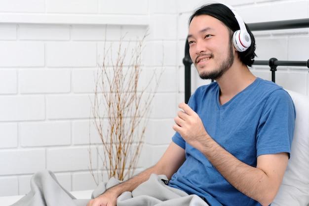 Szczęśliwy młody azjatykci mężczyzna jest ubranym hełmofony słucha muzyka podczas gdy kłamający na białym łóżku w przypadkowej odzieży, ludziach i technologii elektronicznej lifestlye, potomstwa