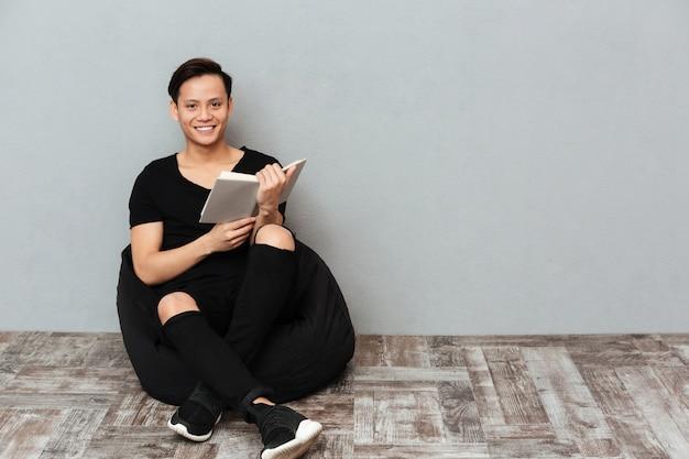 Szczęśliwy młody azjatykci mężczyzna obsiadanie odizolowywający nad szarości ścianą