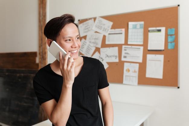 Szczęśliwy młody azjatykci mężczyzna stoi indoors