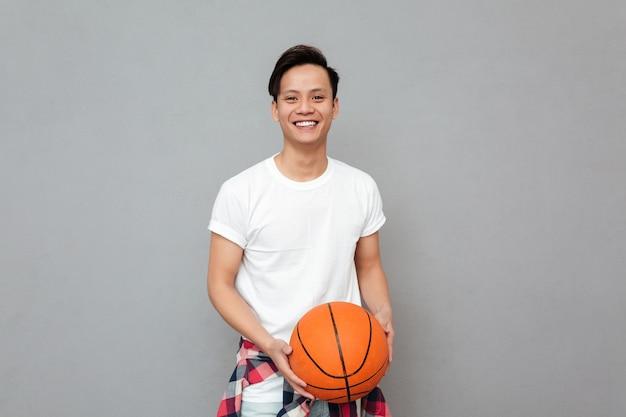 Szczęśliwy młody azjatykci mężczyzna z koszykową piłką