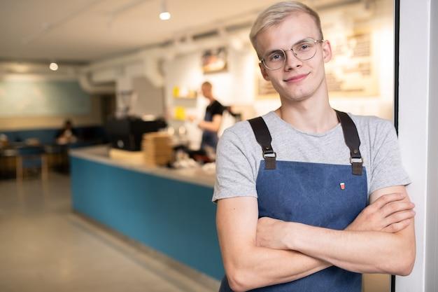 Szczęśliwy młody barista w okularach, szarej koszulce i niebieskim fartuchu skrzyżowanym na ramionach