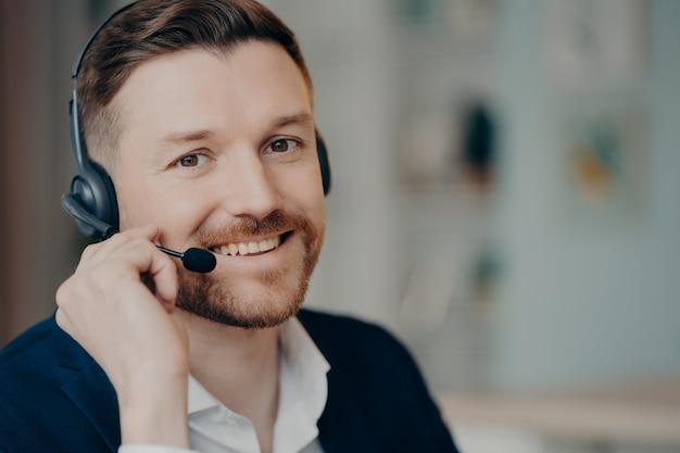 Szczęśliwy młody biznes profesjonalny lub kierownik wykonawczy na sobie garnitur i słuchawki z mikrofonem uśmiecha się do kamery podczas pracy w domu lub w biurze, selektywne focus. koncepcja pracy i zawodu