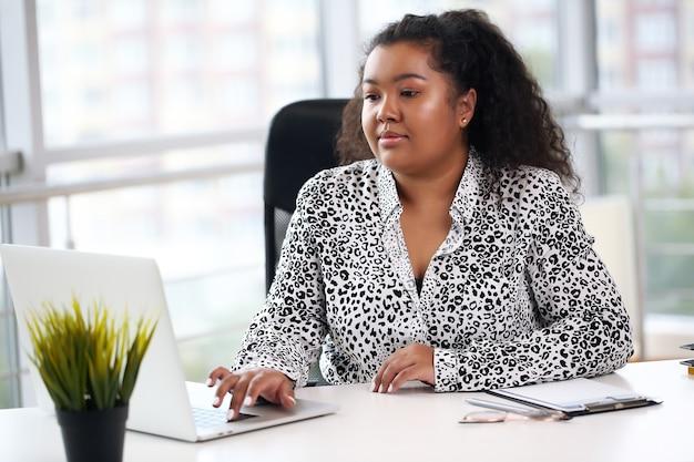 Szczęśliwy młody biznesmen african american za pomocą komputera w biurze.