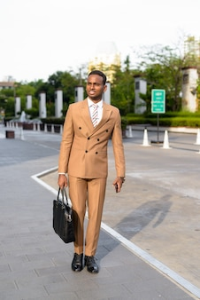 Szczęśliwy młody biznesmen afrykański myśli i gotowy do pracy