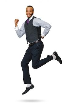 Szczęśliwy młody biznesmen afryki skoki wysoko na białym tle.