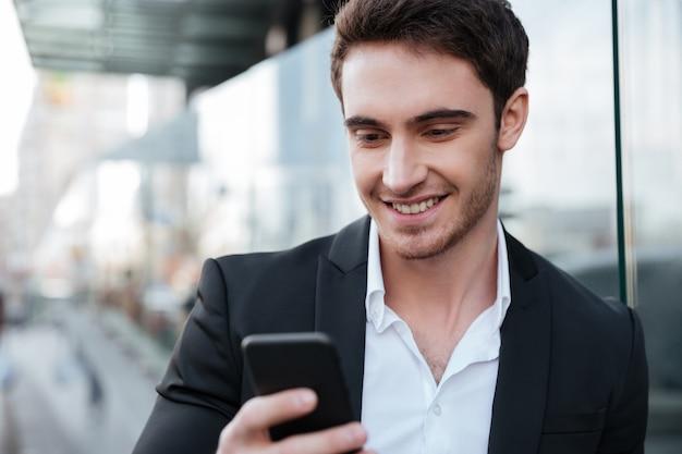 Szczęśliwy młody biznesmen chodzi blisko centrum biznesu gawędzenia