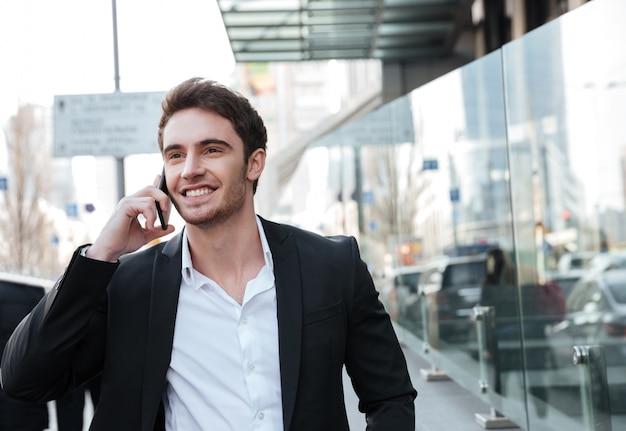 Szczęśliwy młody biznesmen chodzi blisko centrum biznesu