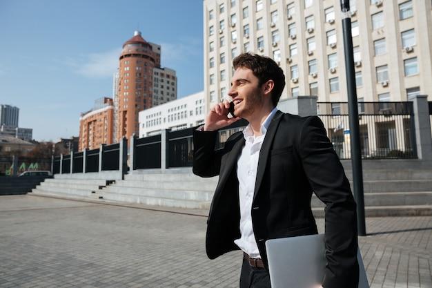 Szczęśliwy młody biznesmen chodzi outdoors opowiadać telefonem.