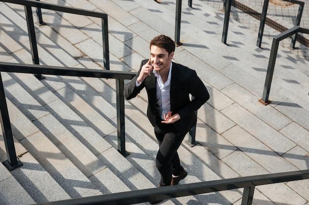 Szczęśliwy młody biznesmen chodzi outdoors