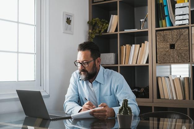 Szczęśliwy młody biznesmen kaukaski uśmiechający się, pracujący online, oglądając podcast webinarowy na laptopie i kurs edukacji, połączenia konferencyjne, robić notatki, siedzieć przy biurku, koncepcja e-learningu