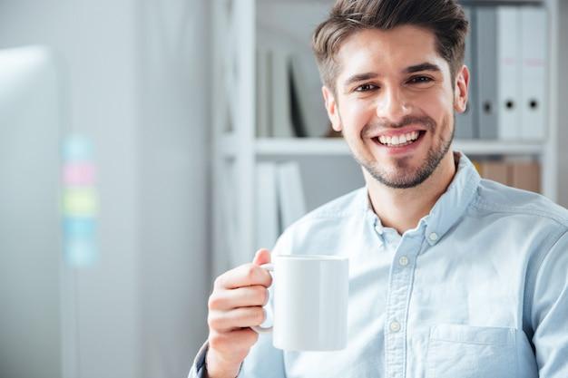 Szczęśliwy młody biznesmen korzystający z laptopa w biurze i patrzący na kamerę