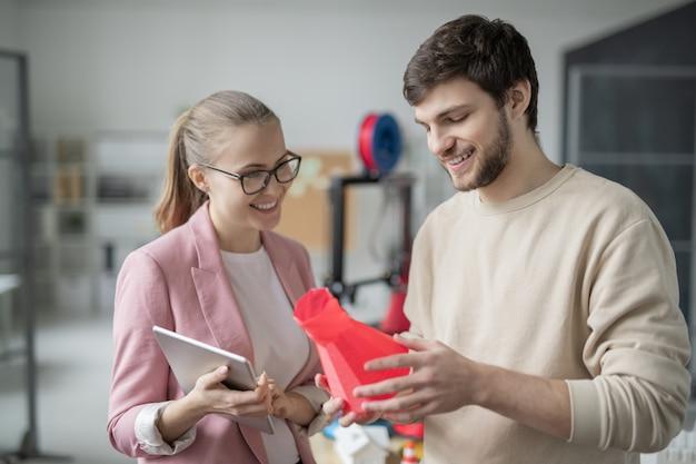 Szczęśliwy młody biznesmen pokazując czerwony obiekt geometryczny właśnie wydrukowany w drukarce 3d swojemu koledze podczas prezentacji