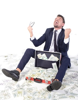 Szczęśliwy młody biznesmen rzuca pieniądze up w formalwear.