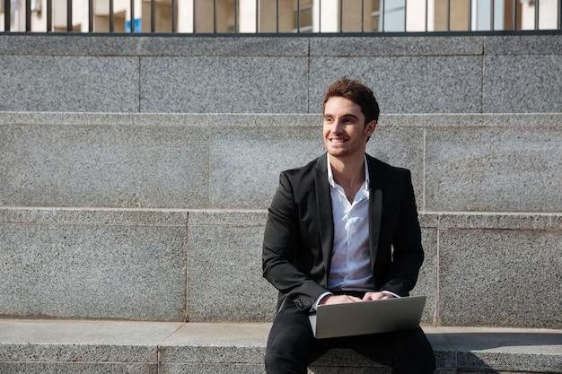 Szczęśliwy młody biznesmen siedzi outdoors używać laptop
