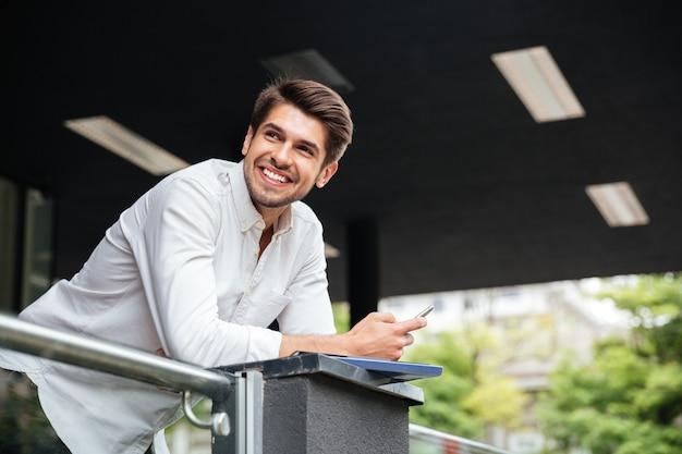 Szczęśliwy młody biznesmen stojący i używający smartfona w pobliżu centrum biznesowego