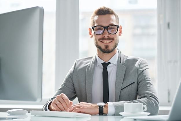 Szczęśliwy młody biznesmen sukcesu w okularach i garniturze siedzi przy biurku przed monitorem komputera