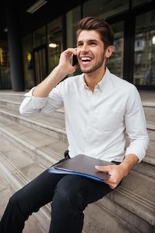 Szczęśliwy młody biznesmen trzyma folder z dokumentami i rozmawia przez telefon komórkowy na zewnątrz