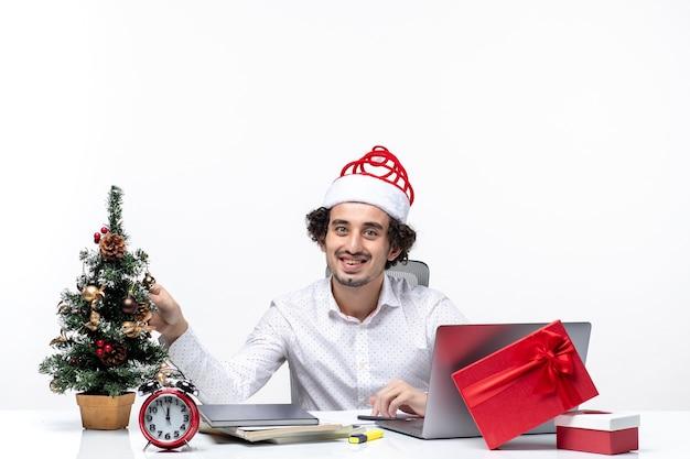 Szczęśliwy młody biznesmen z zabawnym czapką świętego mikołaja ozdabia choinkę i obchodzi boże narodzenie w biurze na białym tle