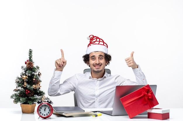 Szczęśliwy młody biznesmen z zabawnym czapką świętego mikołaja, wskazując powyżej i robi ok gest w biurze na białym tle