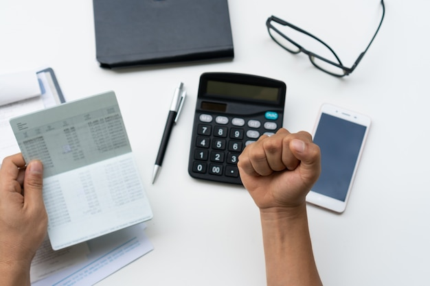 Szczęśliwy młody biznesowego mężczyzna mienia oszczędzania konta passbook na białym biurku w domu