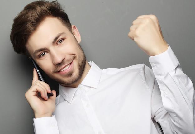 Szczęśliwy młody biznesowy mężczyzna gestykuluje i ono uśmiecha się w koszula.