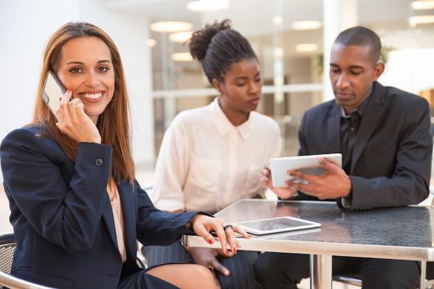 Szczęśliwy młody bizneswoman opowiada na telefonie komórkowym w kawiarni