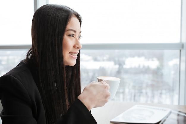 Szczęśliwy młody bizneswoman pije kawę blisko okno w biurze