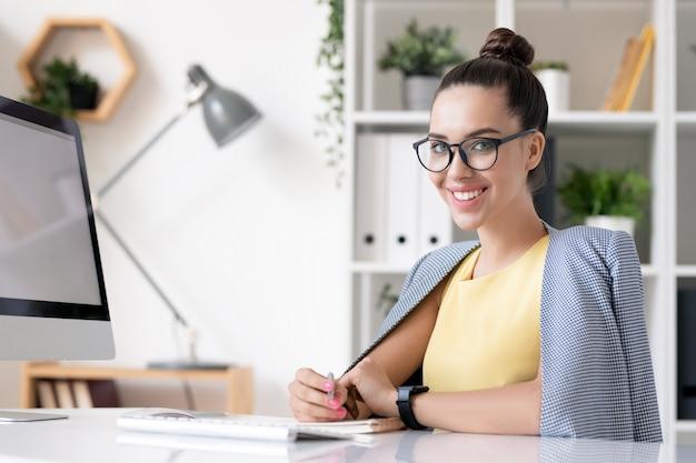 Szczęśliwy młody bizneswoman w inteligentny dorywczo patrząc na ciebie siedząc przy biurku przed kamerą i planując pracę w biurze