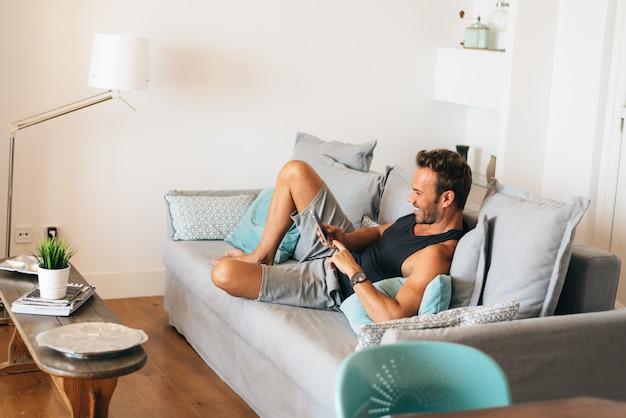 Szczęśliwy młody blondynka mężczyzna siedzi w kanapie w domu na telefonie komórkowym