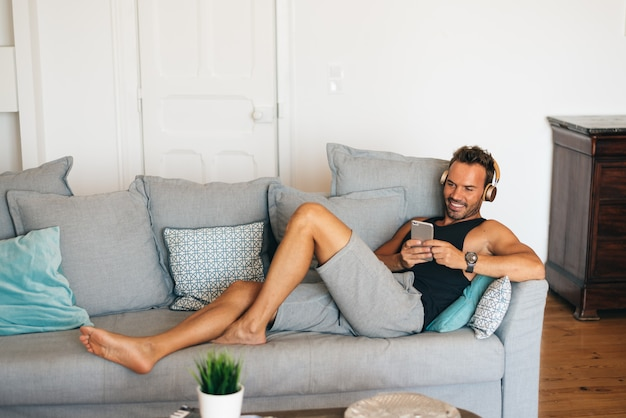 Szczęśliwy młody blondynka mężczyzna siedzi w leżance w domu na telefon komórkowy słuchającej muzyce