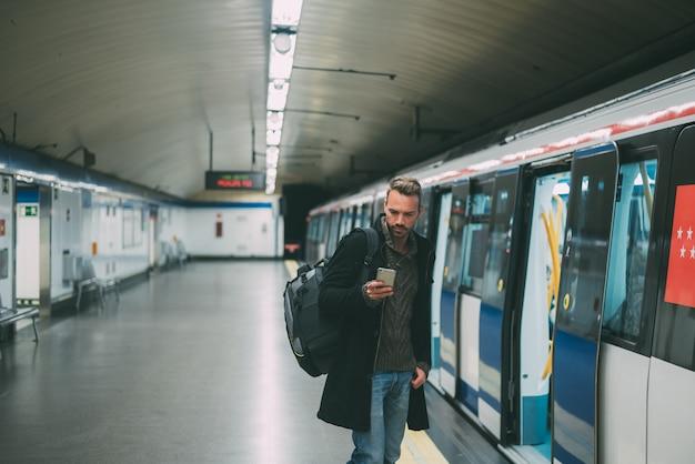 Szczęśliwy młody blondynka mężczyzna z plecakiem wśrodku staci metru czeka pociąg