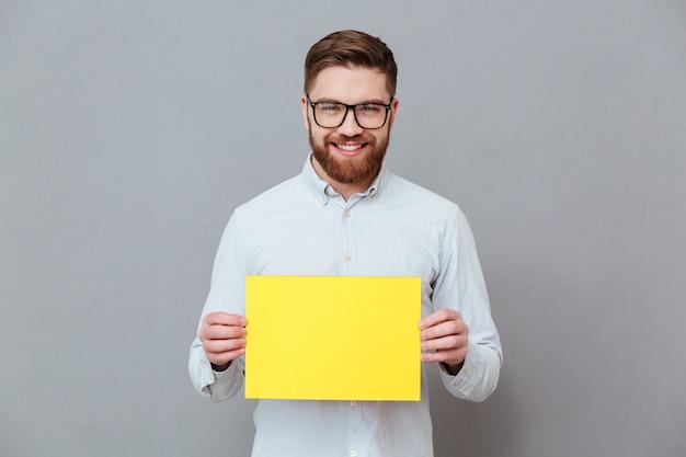 Szczęśliwy młody brodaty biznesmen trzyma pustego papier