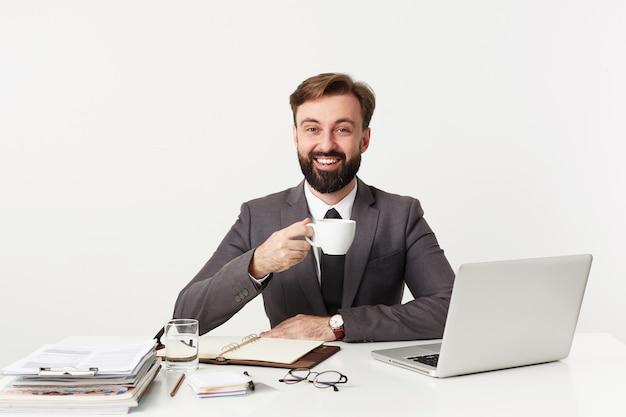 Szczęśliwy młody brodaty biznesmen z krótkimi brązowymi włosami pracuje w nowoczesnym biurze, pijąc kawę przed spotkaniem, uśmiechając się radośnie do przodu, siedząc nad białą ścianą