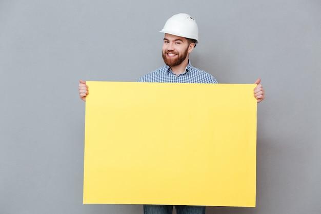Szczęśliwy młody brodaty budowniczego mienia pustego miejsca deska