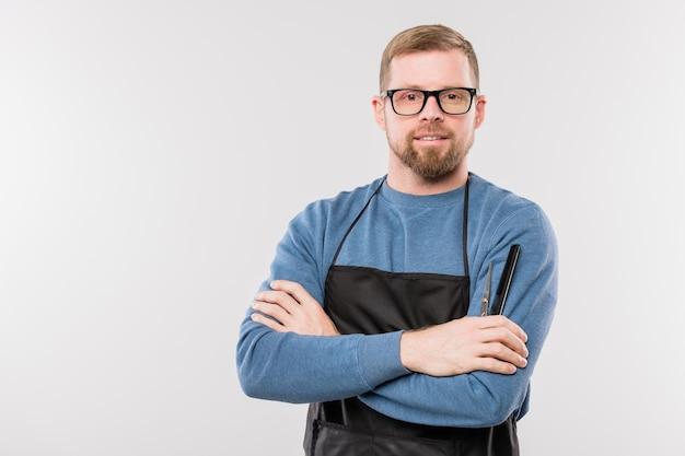 Szczęśliwy młody brodaty fryzjer w fartuch i okulary skrzyżowane ramiona przy klatce piersiowej, stojąc przed kamerą w izolacji
