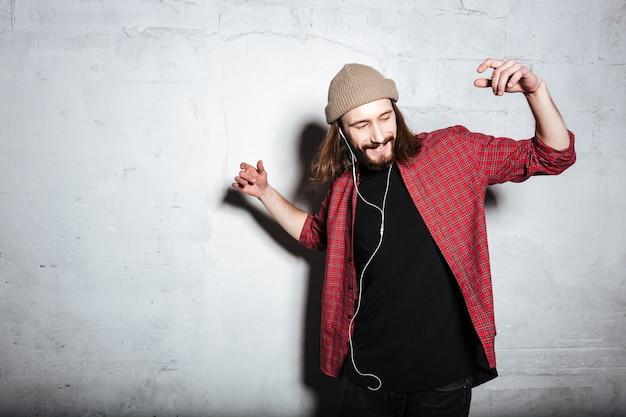 Szczęśliwy młody brodaty hipster mężczyzna w kapeluszu ubrany w koszulę w klatce odizolowanej nad ścianą podczas słuchania muzyki przez słuchawki