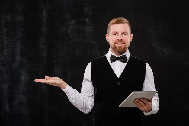 Szczęśliwy młody brodaty kelner z cyfrowym tabletem pokazuje, gdzie iść, stojąc przed kamerą