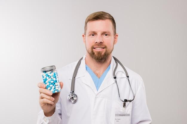 Szczęśliwy młody brodaty lekarz ze stetoskopem trzymając butelkę z pigułkami, stojąc przed kamerą w izolacji