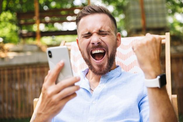 Szczęśliwy młody brodaty mężczyzna na zewnątrz za pomocą telefonu