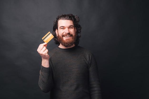 Szczęśliwy młody brodaty mężczyzna trzyma kartę kredytową patrząc w pobliżu czarnej ściany