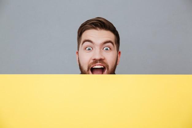 Szczęśliwy młody brodaty mężczyzna trzyma puste miejsce deskę