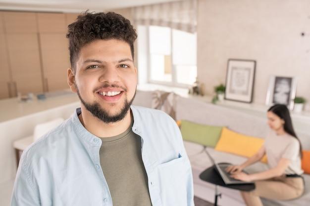 Szczęśliwy młody brodaty mężczyzna w casualwear, patrząc na ciebie z uśmiechem zębów przeciwko swojej żonie siedzącej na kanapie i używającej laptopa w salonie