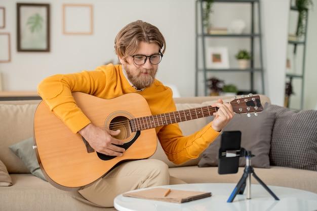 Szczęśliwy młody brodaty mężczyzna w okularach, dżinsach i swetrze, patrząc w aparat smartfona podczas lekcji gry na gitarze online