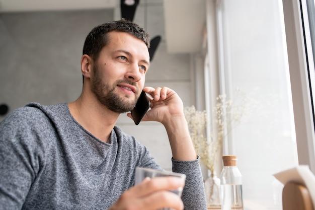 Szczęśliwy młody brodaty mężczyzna w swetrze komunikuje się z kimś na telefon komórkowy podczas relaksu w kawiarni