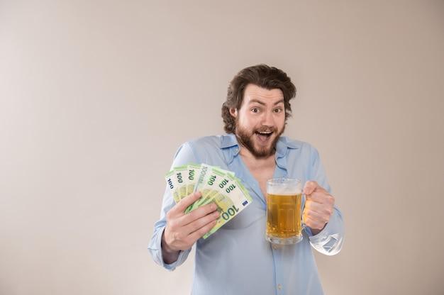 Szczęśliwy młody brodaty mężczyzna z banknotami 100 euro i kuflem piwa na białym tle na szarym tle