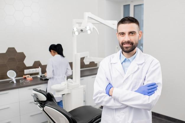 Szczęśliwy młody brodaty profesjonalny dentysta w rękawiczkach i białym płaszczu stojąc przed kamerą na tle swojego asystenta