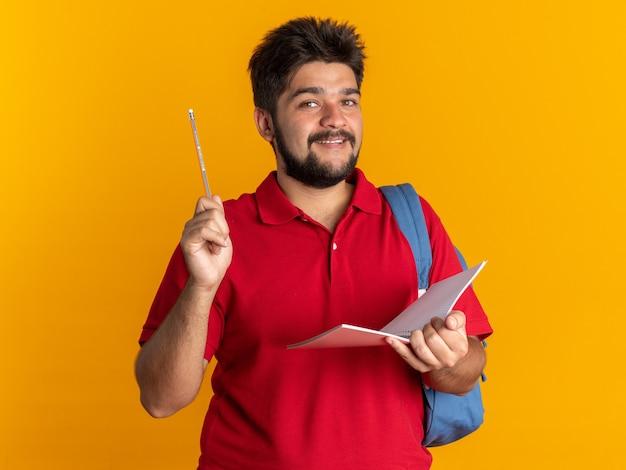 Szczęśliwy młody brodaty student w czerwonej koszulce polo z plecakiem trzymającym notatnik i ołówek patrzący uśmiechnięty radośnie stojący