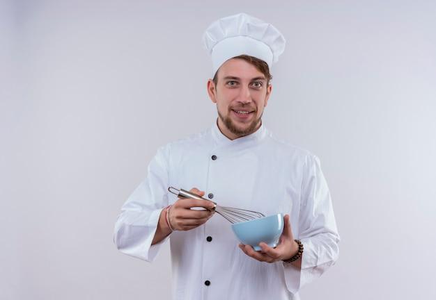 Szczęśliwy młody brodaty szef kuchni ubrany w biały mundur kuchenki i kapelusz trzyma niebieską miskę z łyżką miksera, patrząc na białej ścianie